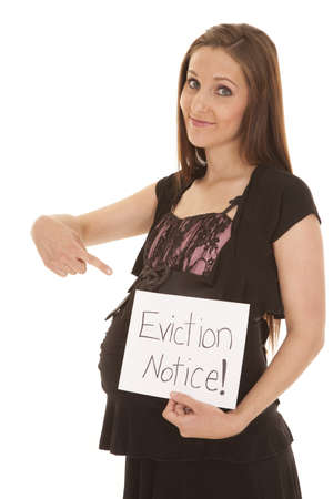 eviction: A woman with a big smile on her face pointing down at her belly and to the eviction notice Stock Photo
