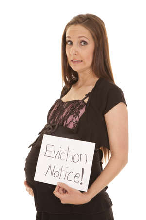 eviction: a woman with a scared expression on her face while holding an eviction notice Stock Photo