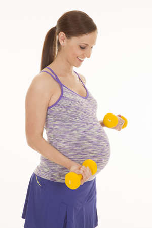 a pregnant woman working out with her yellow weights being fit with a smile on her face. photo