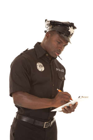 A policeman writing a ticket looking down with a serious expression.