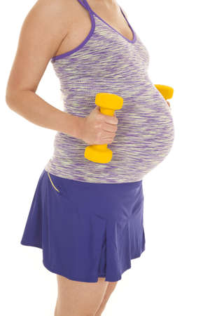 a woman with her weights next to her belly wanting to be a healthy mom. photo