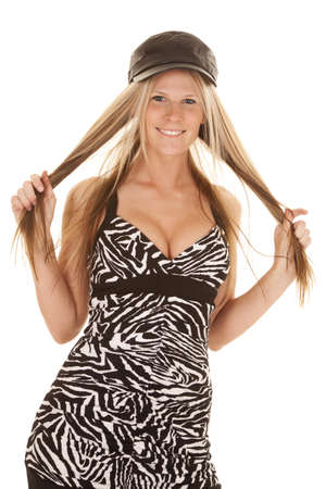 A woman in her zebra dress and black hat playing with hair.