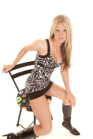 A woman sitting on her stool leaning out in her zebra printed dress with boots photo