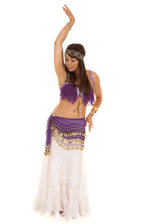 A woman belly dancing in her purple dress showing off her moves. photo