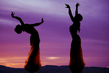 A silhouette of two women belly dancing. photo