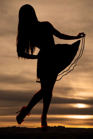 a silhouette of a woman holding on to her skirt