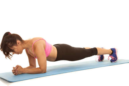plank position: a woman stretching out her body in low plank to workout her whole body