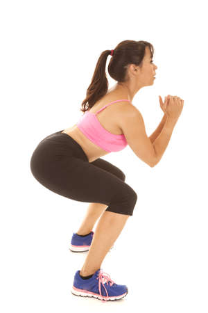 side: A woman doing her leg and butt workout by doing a squat