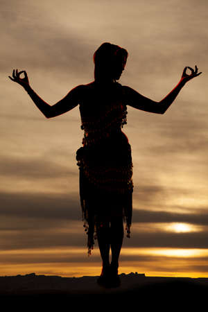 A silhouette of a woman in her gypsy outfit meditating photo