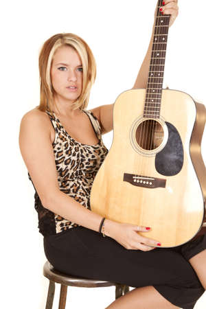 A woman sitting on a stool holding on to her guitar with a serious expression on her face. photo