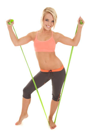 A woman with a smile on her face using her exercise band. photo