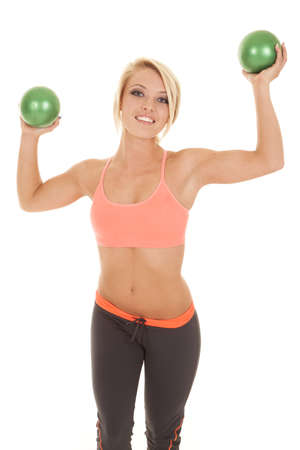 weighted: a woman with a smile on her face holding up her green weighted balls.