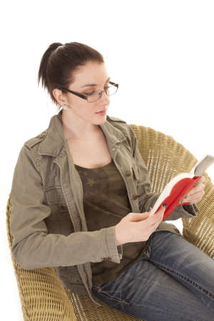 a woman sitting in a wicker chair reading a book Stock Photo - 21223985