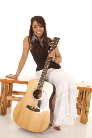 A woman sitting on a bench holding onto her guitar with a smile on her lips photo