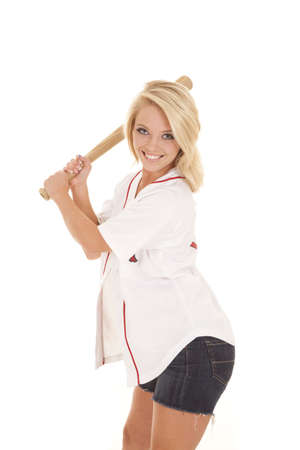 A woman in her baseball jersey holding on to her bat with a smile on her face photo
