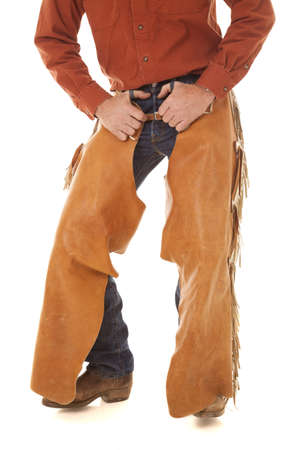 A cowboy is standing with his hands in his belt loops.