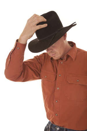A cowboy is holding a black hat on his head.