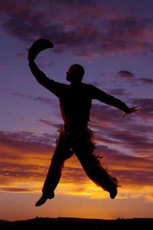 A cowboy is holding his hat and jumping in the sunset. photo