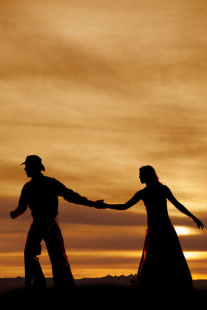 A cowboy and woman in the sunset holding hands. photo