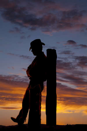 A cowboy is leaning back on a post. photo