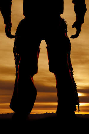 A cowboys legs silhouetted in the sunset.