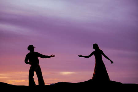 A cowboy is reaching back for a woman in the sunset. Stock Photo
