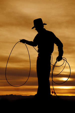 A cowboy is standing in the sunset with a rope in his hands. photo