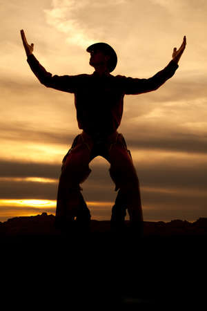 A cowboy is standing with his hands up in the air silhouetted in the sunset. photo