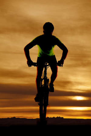 A man on a bike in the sunset riding. photo