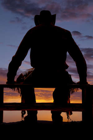 A cowboy in the sunset sitting on a fence. Standard-Bild