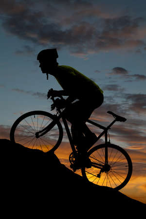 A silhouette of a man climbing a hill on a bicycle.
