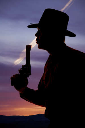 A cowboy is silhouetted with a pistol blowing on the end. photo