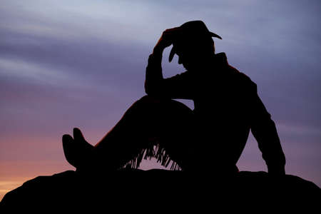 A cowboy is sitting and holding his hat.