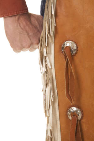 A close up of a cowboys fist and chaps