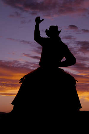 A cowboy is on a horse bucking in the sunset. photo