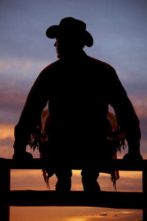 A cowboy is sitting on the fence silhouetted.
