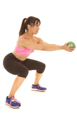 A woman doing a squat holding on to a weighted green ball Foto de archivo
