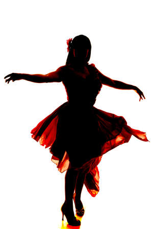 A silhouette of a woman dancing in her flowing dress. photo