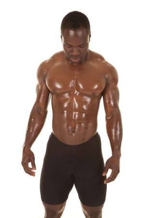 An African American man without a shirt looking down. Stock Photo