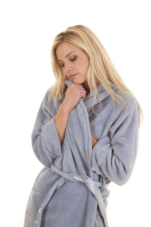 A woman in a blue bathrobe looking down and serious.