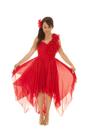 a woman holding out her red dress looking down. Stock Photo - 21268961
