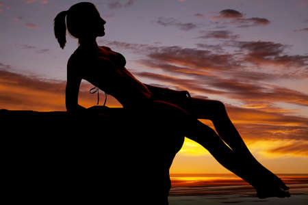 A silhouette of a woman sitting on a rock by the water. Stock Photo - 21268977