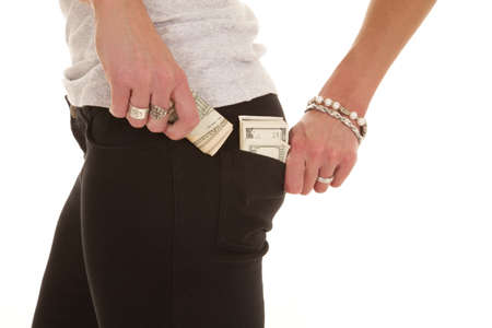 A woman pulling a wad of money from her back pocket. 版權商用圖片