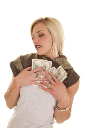 A woman is holding money to her chest. photo
