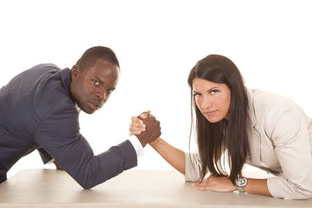 female wrestling: A business man and woman arm wrestling with serious expressions on their faces. Stock Photo