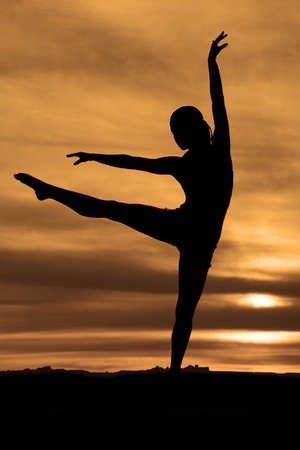 A silhouette of a woman doing a dance pose in the outdoors