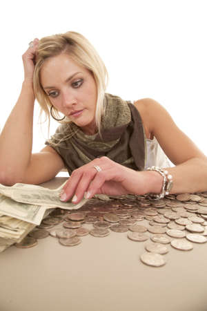 A woman is sitting at a table with money. photo