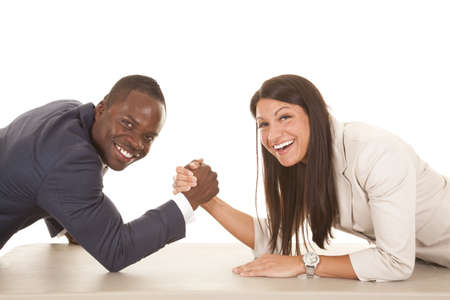 A business man and woman arm wrestling with smiles on their faces. photo