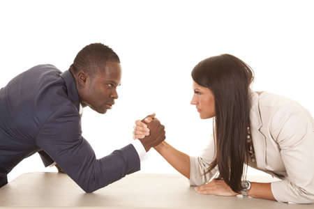 A business man and woman arm wrestling with serious expressions on their faces. photo