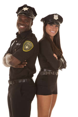 A male cop and a female cop with their backs together and arms folded photo